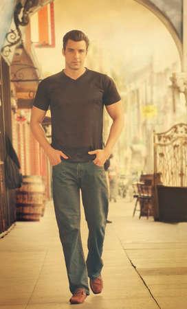 Young male fashion model walking in street scene with retro vintage toning Standard-Bild