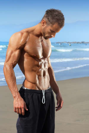 Muscular and fit young bodybuilder fitness male model on beach