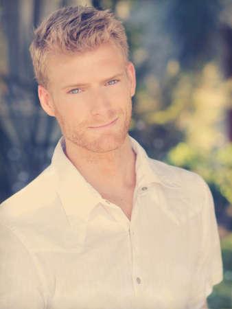 Portrait d'un beau jeune homme avec un sourire chaleureux en chemise blanche décontractée avec rétro tonification et le style global Banque d'images