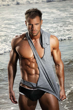 Hot handsome young man with fit muscular body in front of ocean water photo