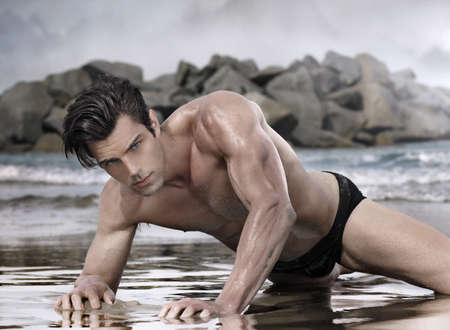 Beau modèle glamour mâle sur la plage exotique de mauvaise humeur