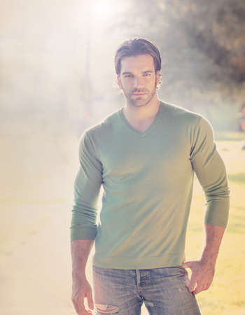 Stylized portrait of a handsome man outdoors with sun flare and haze photo