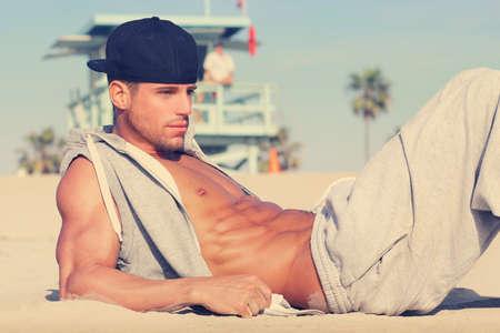modelos hombres: Chico joven caliente en la playa con muy sutil tono retro