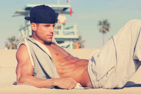 lying on the stomach: Hot young guy at the beach with very subtle retro toning