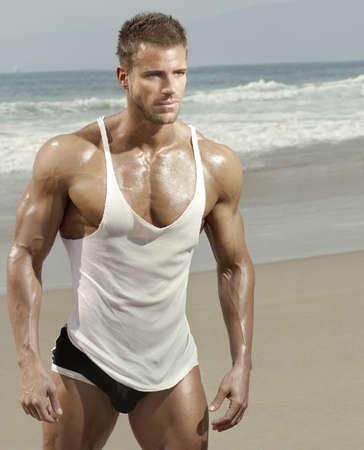 Sexy modèle masculin musculaire sur la plage à la lumière chaude d'été