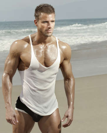 Sexy muscular male model on the beach in warm summer light