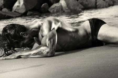 artistic nude: Fine art black and white sensual body portrait of a sexy muscular fit young man laying on beach Stock Photo