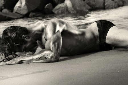nue plage: Noir de beaux-arts et blanc sensuel portrait de corps d'un jeune homme muscl� ajustement sexy s'�tendant sur la plage
