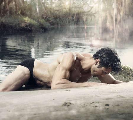 portrait du corps d'un bel homme musclé ajustement sur la rive de la lagune fantastique Banque d'images