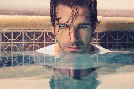 Close up portrait d'un beau jeune homme dans la piscine avec virage subtil cru Banque d'images