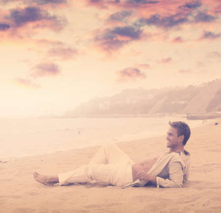 Young happy man with great smile on the beach with dramatic sky and overall vintage toning and styling Foto de archivo