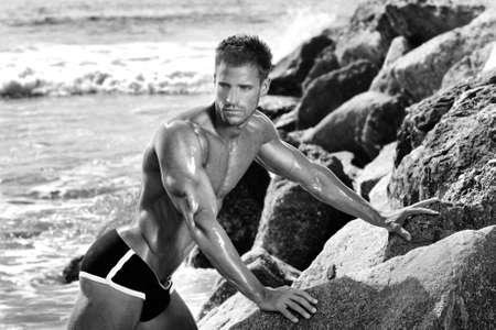 Sexy gespierde bodybuilder poseren in de buurt van rotsen en de oceaan