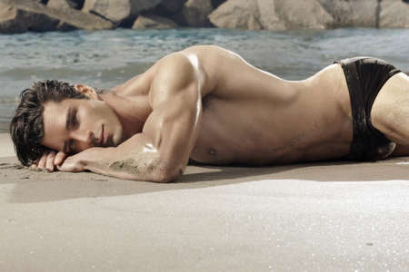 Beatiful fit man laying on exotic beach photo