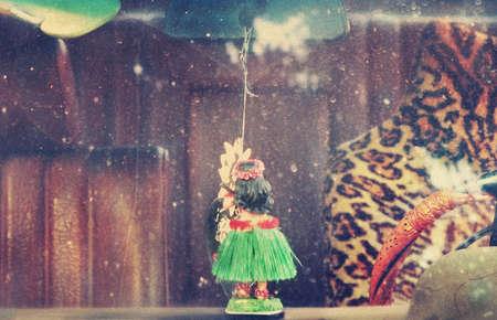 Le concept Cool d'un intérieur de voiture ancienne à travers la fenêtre sale avec tableau de bord hula fille poupée, housse de siège d'impression de léopard, et le vieux cuir - filtrée avec tonification cru authentique et le grain du film