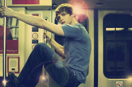 Young man riding subway with overall vintage toning and gritty film grain for true retro look and feel