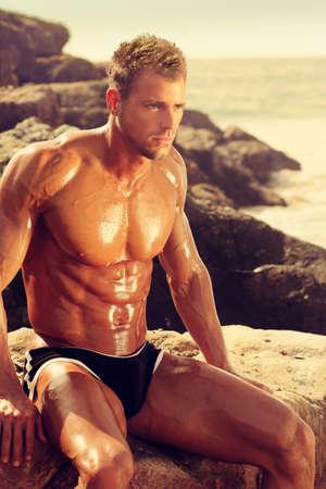 Musucular jeune homme assis sur les rochers à la plage à la lumière d'or Banque d'images