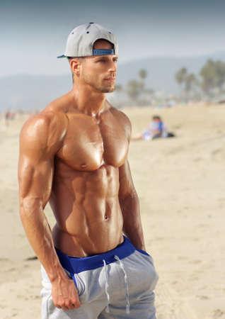 Knappe jonge gespierde mannelijke model op het strand genieten van de zomer Stockfoto