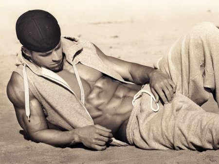 Fit modelo masculino jovem e saudável com grande abs chutando de volta na praia em tons sépia quentes