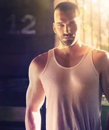 Portrait sexy de l'homme masculin avec la tête rasée en lumière dramatique dur et ombre