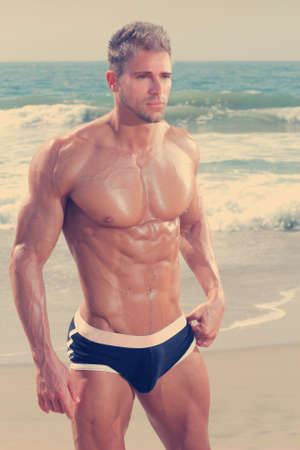 naked male body: Sexy very muscular handsome man in underwear on beach