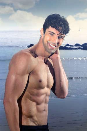 musculoso: Joven guapo modelo masculino con gran cuerpo sonriendo y divertirse al aire libre