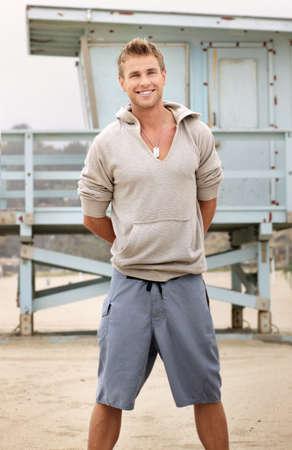 Jeune bon mâle regardant sur la plage avec un beau sourire Banque d'images