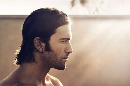 man with long hair: Profile portrait of young rugged man with vintage tone and style