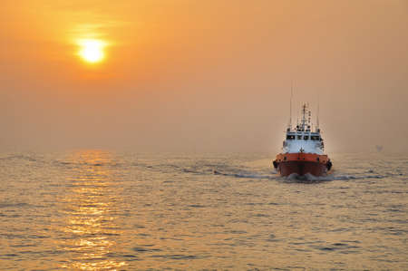 sky dive: Offshore Boat for Crew Change Before Sunset With Stunning Golden Sky Stock Photo