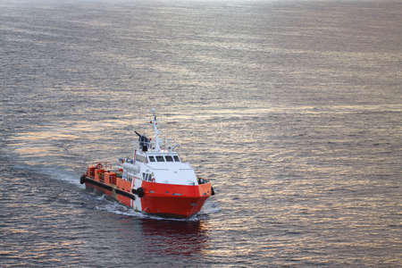 Offshore Boat for Crew Change Before Sunset With Stunning Golden Sky Banque d'images