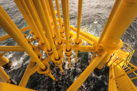 well platform: Oil and Gas Producing Slots at Offshore Platform - Oil and Gas Industry  Bad weather in offshore oil and gas platform  Stock Photo