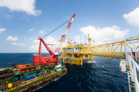 vessels: Large crane vessel installing the platform in offshore,crane barge doing marine heavy lift installation works in the gulf or the sea