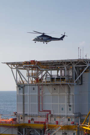 helicopter landing on an offshore oil-plant , service travel to oil and gas platform in offshore photo