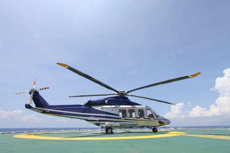 Elicottero parcheggio atterraggio sulla piattaforma off-shore. Trasferimento di equipaggi di elicotteri o passeggero di lavorare nell'industria del petrolio e del gas in mare aperto. Archivio Fotografico - 31631573