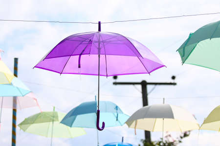 Colorful of umbrellas hang on the sky with blue sky background photo