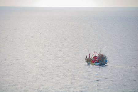 Fishing boat heading out to the gulf in the early morning photo