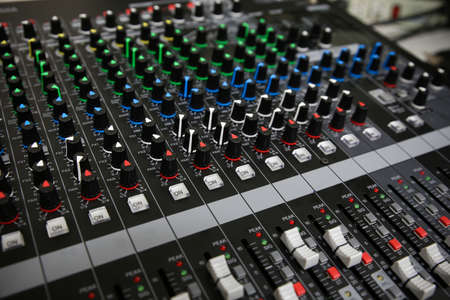 Hand on a Mixing Desk Fader in Television Gallery, Music equipment in training room. Stock Photo