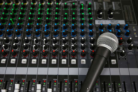 dubbing: Hand on a Mixing Desk Fader in Television Gallery, Music equipment in training room. Stock Photo