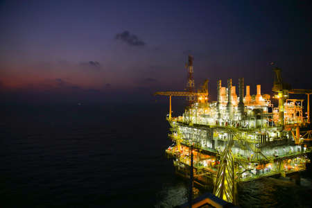 construction platform: oil and gas construction in night view. View from helicopter night flight. Oil and gas platform in offshore