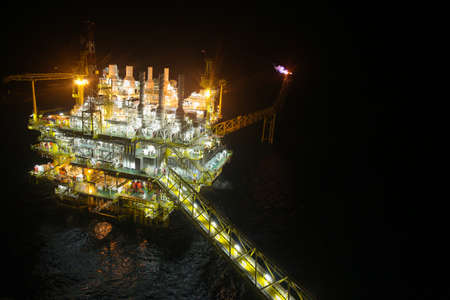 greenhouse gas: oil and gas construction in night view. View from helicopter night flight. Oil and gas platform in offshore