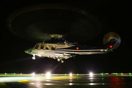 helideck: Helicopter landing in offshore oil and gas platform on deck or parking area. Helicopter night flight training of pilot. Stock Photo