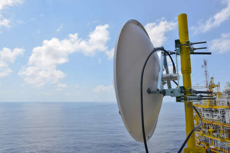 airwaves: Satellite dish antennas under sky, Communication equipment in offshore oil and gas industry. Stock Photo