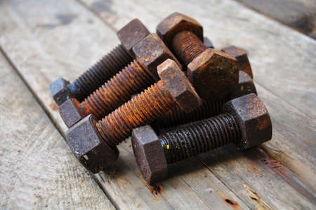 gudgeon: Old bolts or dirty bolts on wooden background, Machine equipment in industry work.