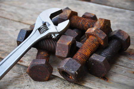 machined: Old bolts with adjustable wrench tools on wooden background.