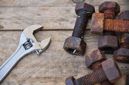 adjustable: Old bolts with adjustable wrench tools on wooden background.