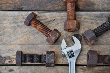 gudgeon: Old bolts with adjustable wrench tools on wooden background.