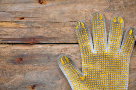 Old safety gloves on wooden background, Gloves on dirty works. photo