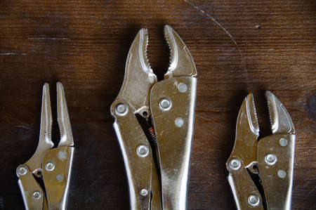 locking up: close up locking pliers on wooden background, Hand tools in work shop. Stock Photo