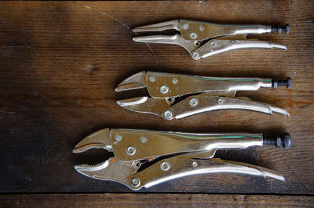 close up locking pliers on wooden background, Hand tools in work shop. photo