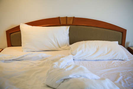 carelessness: Messy and unmade bed in hotel room. White pillows and bed in white bedroom.