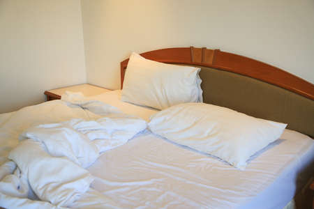 Messy and unmade bed in hotel room. White pillows and bed in white bedroom. photo